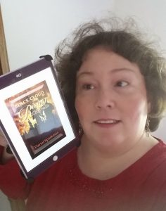 Ronda Del Boccio holding the Kindle edition of Black Cloud Rising: CHrytsalis  by Darrel Sparkman, showing the cover