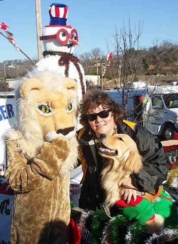 Leader Dog Jemma and author Ronda Del Boccio on the Lions Club float. Behind them, a Snowman wears glasses. Beside them is the mascot Lion.